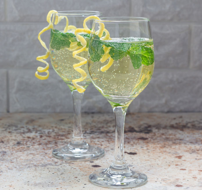 Spritzer cocktail with white wine, mint and ice, decorated with spiral lemon zest, square