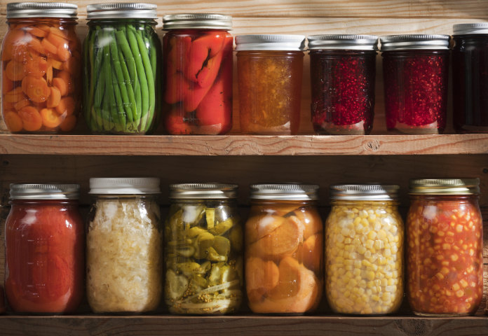 Subject: Two wooden shelves holding a variety of canned vegetables and fruits, lined up in rows