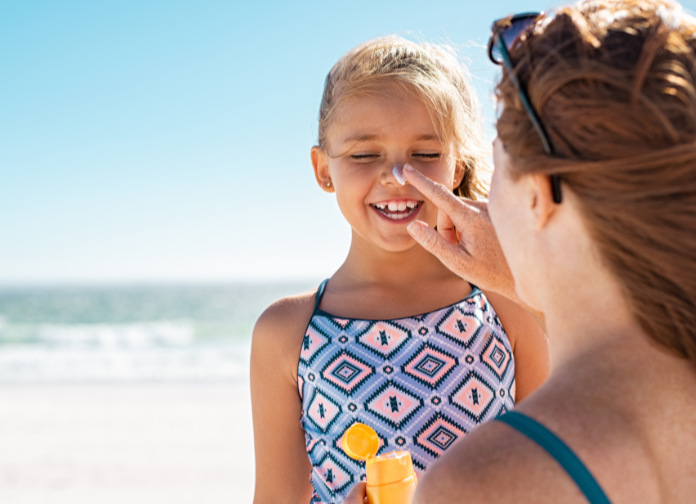 Young mother applying protective sunscreen on daughter nose at beach. Woman hand putting sun lotion on child face. Cute little girl with sunblock at seaside