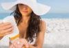Skin cancer facts Woman applying sun cream on the beach