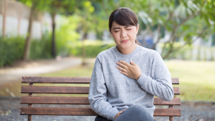 Generic photo of young woman on a park bench experiencing pain in her chest (ThinkStock/PA)