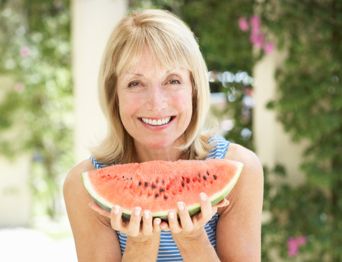 Senior Woman Enjoying Slice Of Water Melon Outdoors Sitting On Table And Smiling To Camera