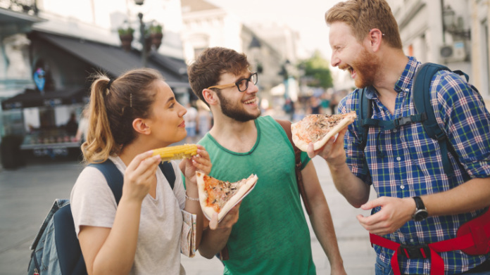 Generic photo of three young people eating pizza at a food market on holiday (ThinkStock/PA)