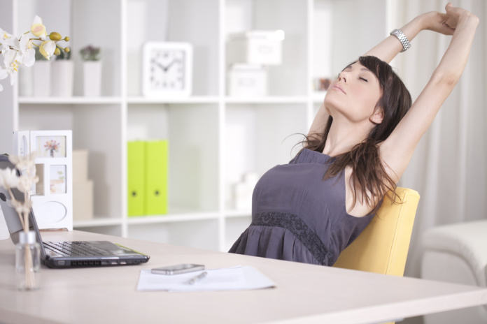 Woman streaching during a break. She work at home.