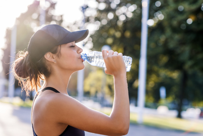 Photo of young Woman drinking water from bottle.