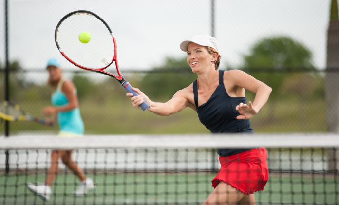 """""""young woman playing Doubles tennis, hitting a forehand volley."""""""