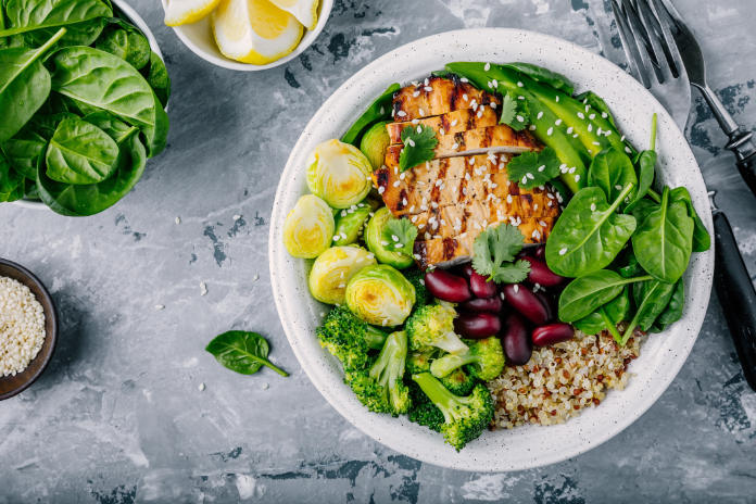 Healthy eating rules Healthy buddha bowl lunch with grilled chicken, quinoa, spinach, avocado, brussels sprouts, broccoli, red beans with sesame seeds