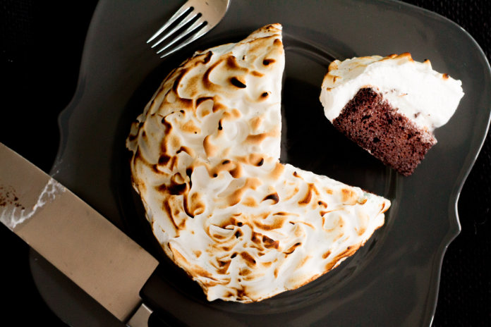 Baked Alaska, sliced and presented on a grey plate with a black background