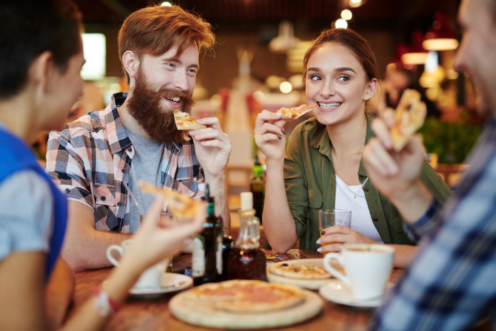 Signs of poor gut health people eating pizza