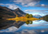 Amazingly still reflections of the island in Loch Leven, Scotland, with the Pap of Glencoe in the middle distance.
