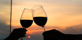 Wine Holidays – Couple with glasses of red wine in luxury restaurant.