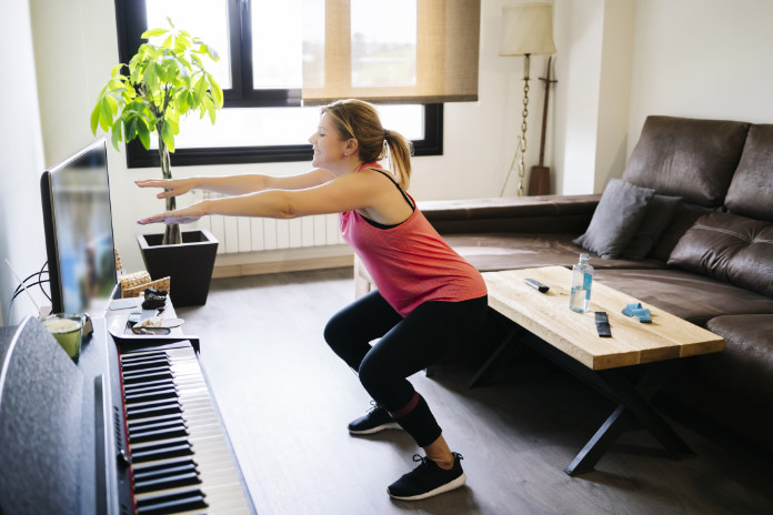woman doing exercises with elastic band in living room at home