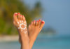 Woman foot with sun-shaped sun cream in the tropical beach