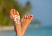 Woman foot with sun-shaped sun cream in the tropical beach