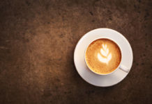 Health benefits of coffee ≠ Cup of cappuccino with perfect latte art on the table.