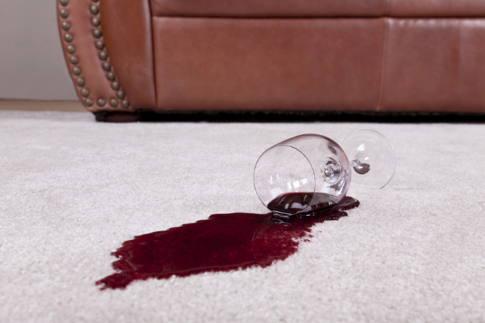A wine glass with a red wine spill creating a puddle rests on a tan loop pile carpet.  The wine glass rests on the spilled wine.  The glass has a long stem and wide base.  The spill fans out from the top of the glass.  The spill appears deeper underneath the glass.