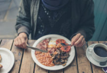 A young woman is having a traditional english breakfast