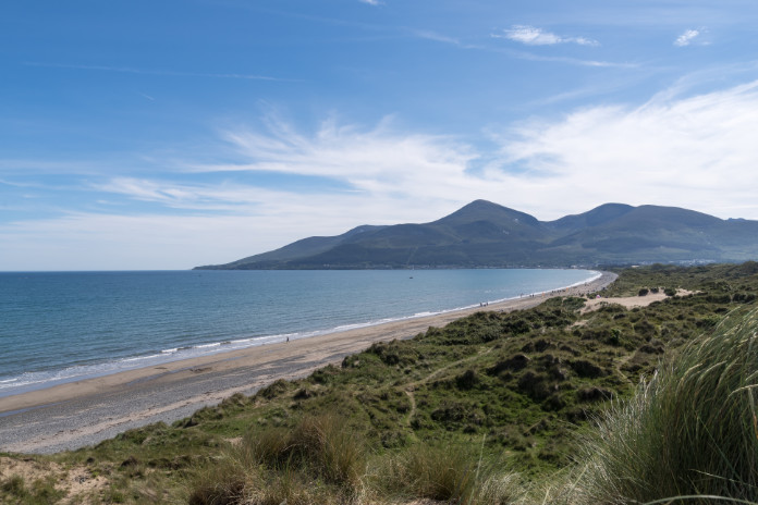 Coastal dunes, beach shoreline, receding tide and the outline of the Mountains of Mourne at Newcastle, County Down, Northern Ireland.