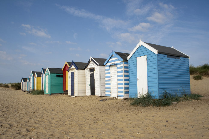 Colourful beach huts against a blue sky at Southwold, Suffolk , England