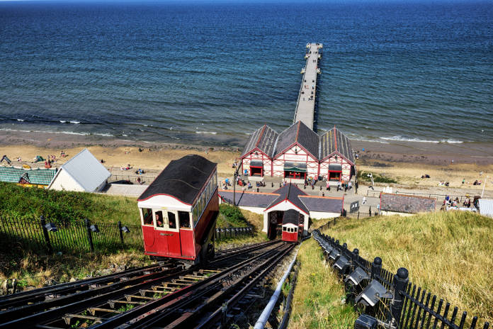 Saltburn by the Sea, England - August 13, 2015: Saltburn Clif Lift, Pier and beach at Saltburn by the Sea in North Yorkshire, England. Many people in distance.