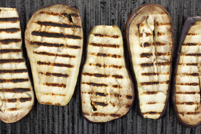 Top view of grilled eggplant slices over iron grill