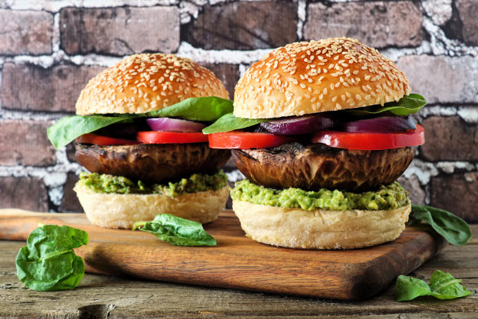 Portobello mushroom vegan burgers with avocado, tomato and spinach and onion on a wood serving board against a dark brick background