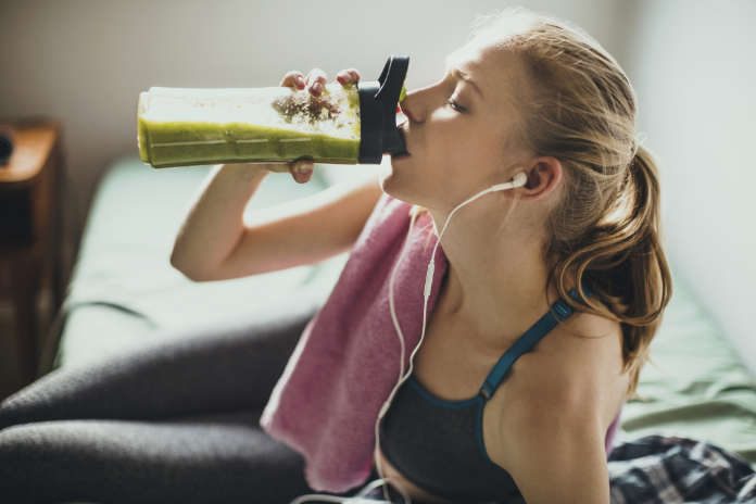Young woman getting having her green smoothie after training