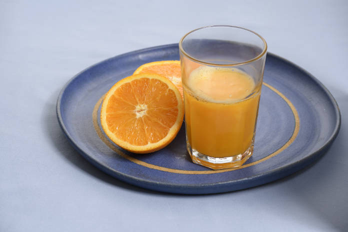 Glass with orange juice having orange next to it