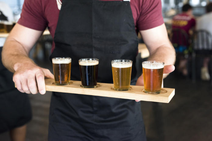 Waiter carrying a tray of glasses filled with different craft beers inside the brewery.