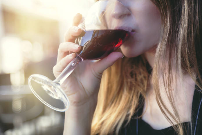 Young woman drinking rose wine