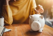 Woman saving money into ceramic piggy bank