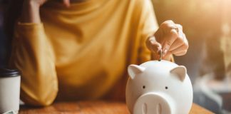 Woman saving money into ceramic piggy bank