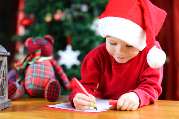 A young boy wearing a red Christmas hat and red sweater is writing a letter to Santa Claus. The child is sitting at a wooden table in front of a Christmas tree.