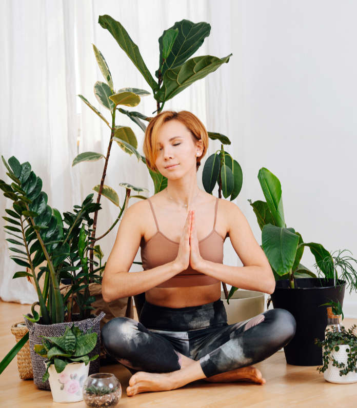 Meditating young happy woman sitting in easy pose, her hands are joined, eyes closed. She is surrounded by lots of potted plant.