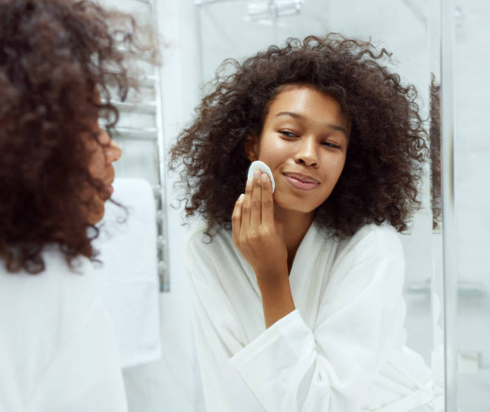 Girl removing makeup with cosmetic cotton pad at bathroom.