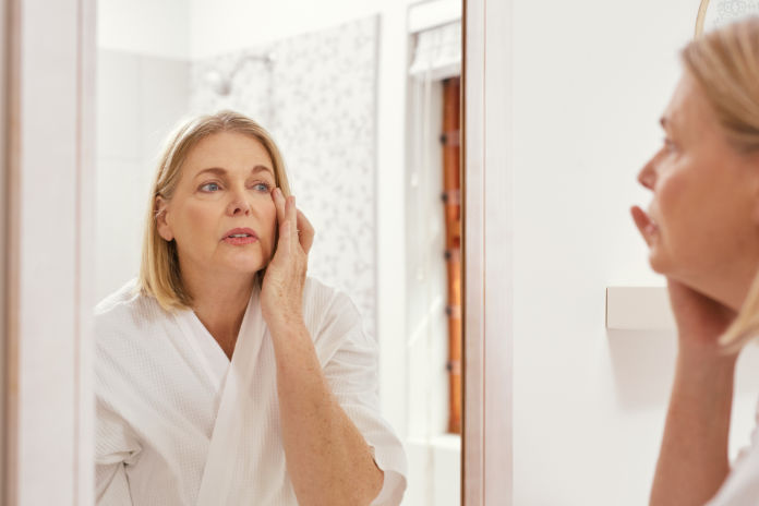 Shot of a mature woman looking at herself in the bathroom