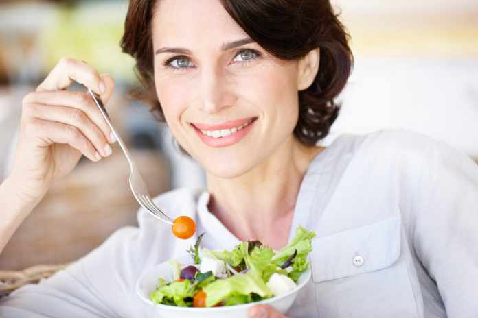A beautiful woman eating a bowl of salad