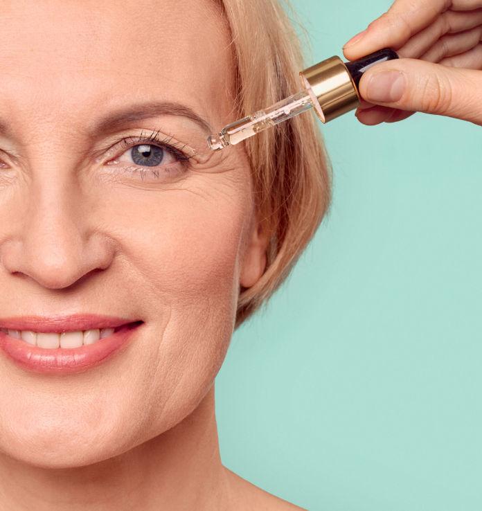 middle aged female applying organic rejuvenation oil on face,
