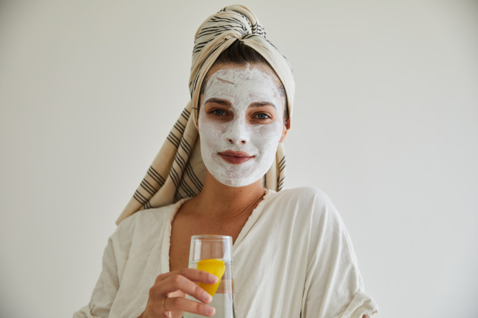 Portrait of a smiling young woman in a bathrobe and wearing a cleansing clay face mask
