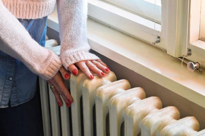 Cosy winter home woman feeling radiator