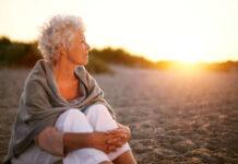Mature woman on beach looking into horizon