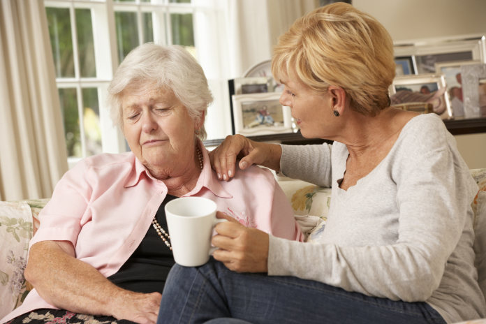 Adult Daughter Visiting Unhappy Senior Mother Sitting On Sofa