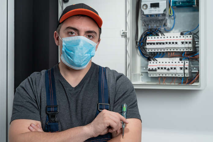 Electrician with N95 protective mask  looking at camera in front fuse box.