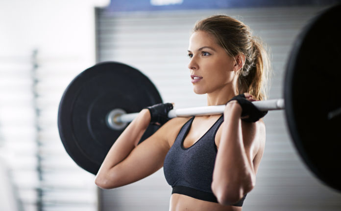 Shot of a young woman working out with a barbell at the gym