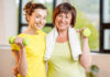 Exercise with a friend Young and older women in sportswear training with dumbbells indoors on the window background