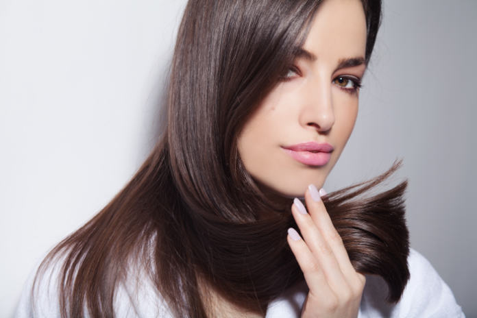 oung woman holding her healthy and shiny hair,