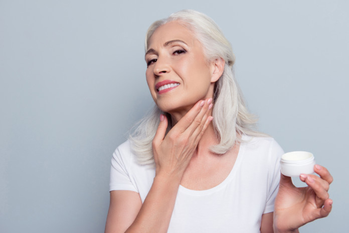 Mature adult senior woman with gray hair is taking care about her face and neck