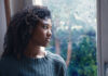 Dealing with seasonal Affective Disorder - young worried woman looking out of the window