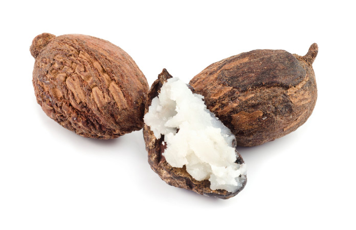 three shea nuts, one is filled with butter.