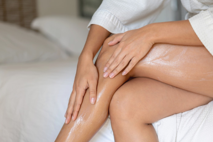 Close-up on a woman applying moisturizing shea butteron her legs